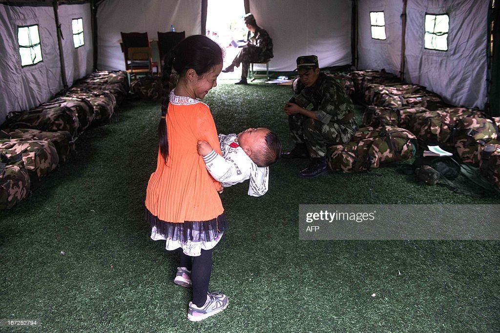 This photo taken on April 22, 2013 shows a little girl playing with a baby in a tent at the temporary settlement in Lingguan Middle School in Baoxing county of Yaan, southwest China's Sichuan province. Clogged roads, debris and landslides impeded rescuers on April 22 as they battled to find survivors of a powerful earthquake in mountainous southwest China that has left at least 192 dead. CHINA