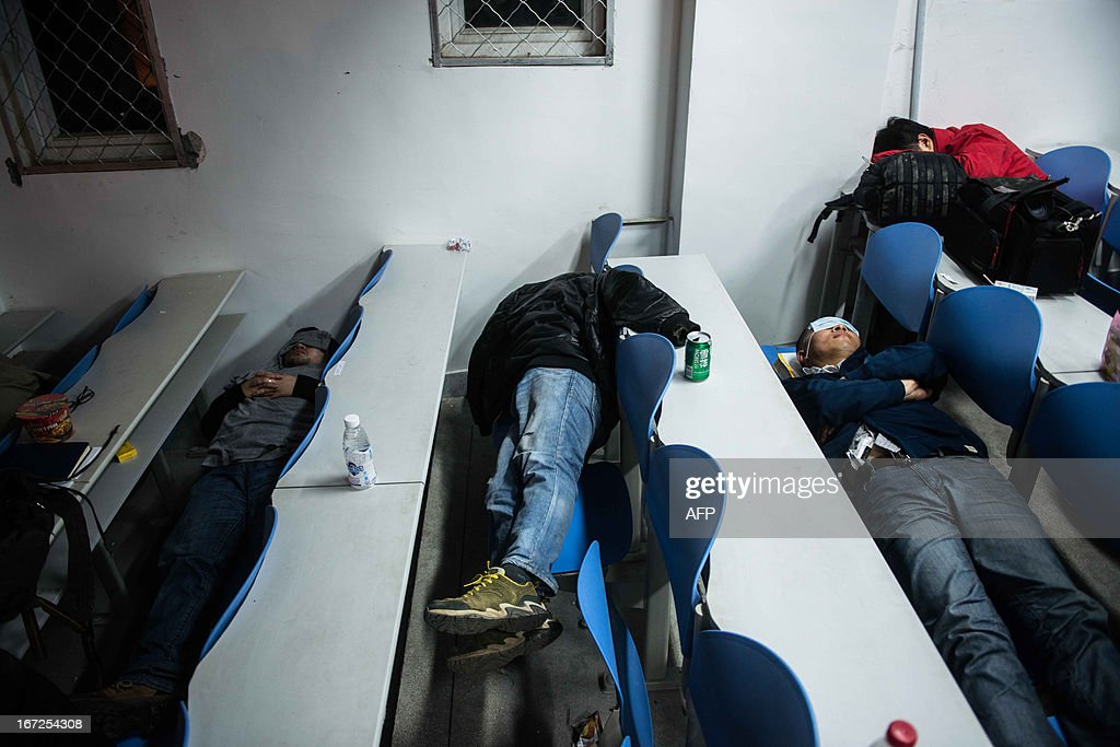 This photo taken on April 22, 2013 shows journalists sleeping on classroom seats at a temporary settlement in Lingguan Middle School in Baoxing county of Yaan, southwest China's Sichuan province. Clogged roads, debris and landslides impeded rescuers on April 22 as they battled to find survivors of a powerful earthquake in mountainous southwest China that has left at least 192 dead. CHINA