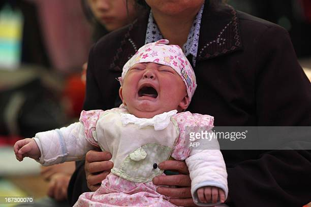 This photo taken on April 23 2013 shows 4monthold Li Jie crying in her mother's arms inside a temporary settlement in Lingguan township of Baoxing...