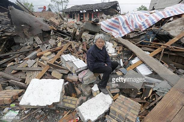 This photo taken on April 23 2013 shows an elderly woman sitting on debris in a disasterhit area in Ya'an in southwest China's Sichuan province days...