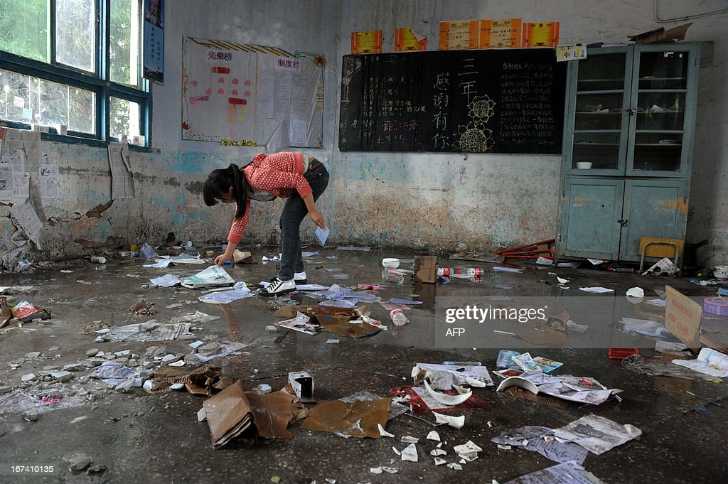 This photo taken on April 24, 2013 shows a girl picking up books in an earthquake damaged school in Ya'an, southwest China's Sichuan province. Tens of thousands of homeless survivors of China's devastating quake are living in makeshift tents or on the streets, facing shortages of food and supplies as well as an uncertain future. CHINA