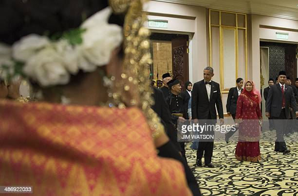 This photo taken on April 26 2014 shows US President Barack Obama walking with Malaysian Sultan Abdul Halim of Kedah and Queen Haminah as they arrive...
