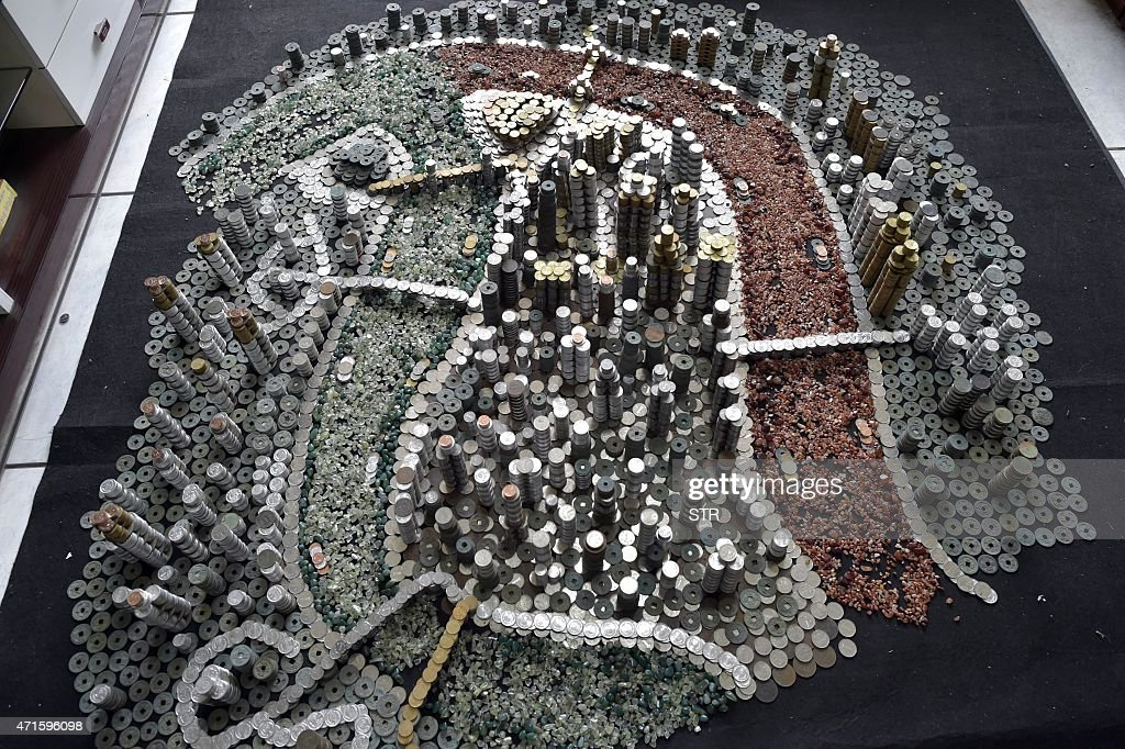 This photo taken on April 29 2015 shows a replica of Chongqing built by local resident He Peiqi with coins and agate stones in his home in China's...