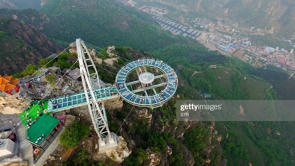 This photo taken on April 30, 2016 shows a glass sightseeing platform in Shilinxia scenic spot in Pinggu District of Beijing. The sightseeing platform, which hangs 32.8 meters out from the cliff, is claimed to be the largest glass sightseeing platform in the world. / AFP / STR / China OUT