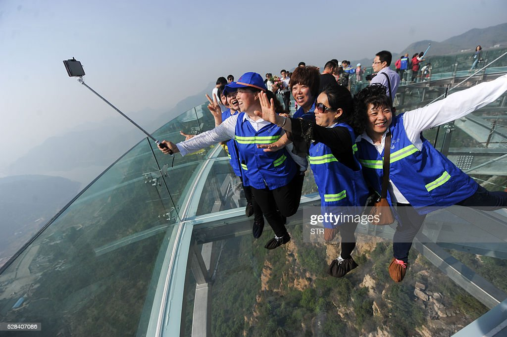 This photo taken on April 30, 2016 shows people posing on a glass sightseeing platform in Shilinxia scenic spot in Pinggu District of Beijing. The sightseeing platform, which hangs 32.8 meters out from the cliff, is claimed to be the largest glass sightseeing platform in the world. / AFP / STR / China OUT