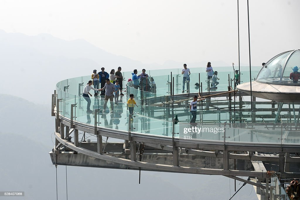 This photo taken on April 30, 2016 shows people walking around a glass sightseeing platform in Shilinxia scenic spot in Pinggu District of Beijing. The sightseeing platform, which hangs 32.8 meters out from the cliff, is claimed to be the largest glass sightseeing platform in the world. / AFP / STR / China OUT