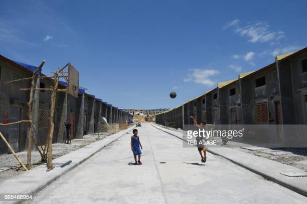 TOPSHOT This photo taken on April 5 2017 shows young boys playing basketball next to houses originally built by the government for soldiers and...