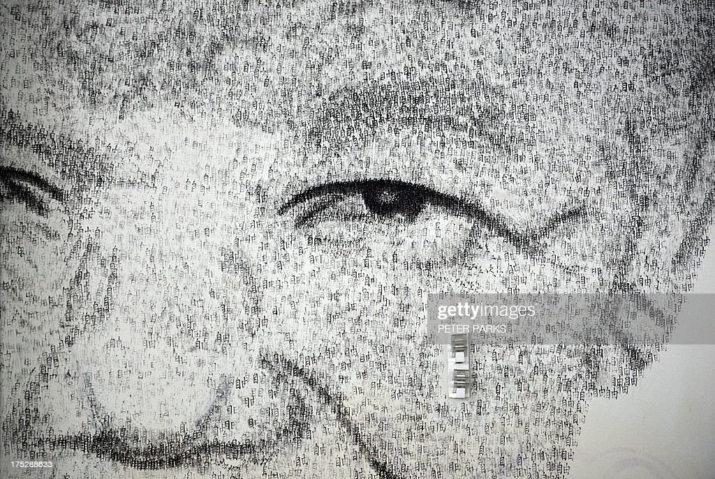 This photo taken on August 1, 2013 shows a close up detail of Shanghai based 34 year-old Belgian artist Phil Akashi's portrait of South African peace icon and former boxer Nelson Mandela, which he forged by pounding the wall 27,000 times with a boxing glove which bore the Chinese character for 'freedom', in Shanghai. Mandela, who's 95th birthday earlier this month was marked in South Africa by an outpouring of charitable deeds, with many people offering 67 minutes of service for the 67 years he was in public service, continues to show signs of improvement after two months of hospital treatment. AFP PHOTO / Peter PARKS CAPTION
