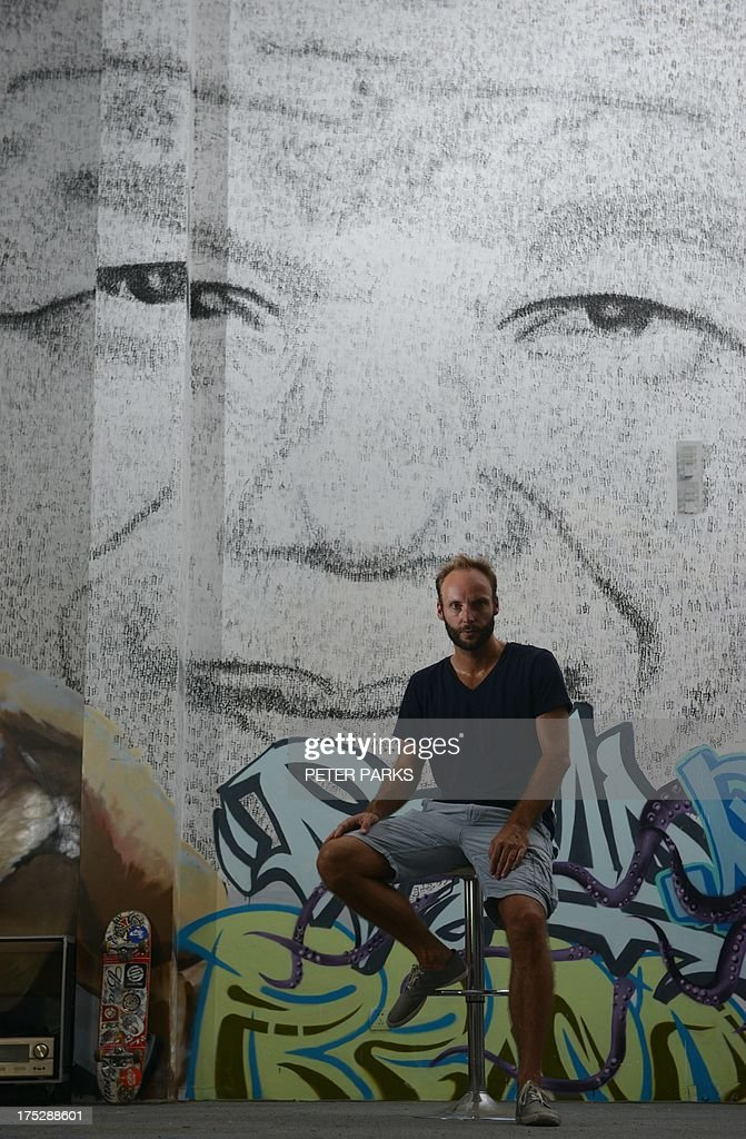 This photo taken on August 1, 2013 shows Shanghai based 34 year-old Belgian artist Phil Akashi sitting in front of his portrait of South African peace icon and former boxer Nelson Mandela, which he forged by pounding the wall 27,000 times with a boxing glove which bore the Chinese character for 'freedom', in Shanghai. Mandela, who's 95th birthday earlier this month was marked in South Africa by an outpouring of charitable deeds, with many people offering 67 minutes of service for the 67 years he was in public service, continues to show signs of improvement after two months of hospital treatment. AFP PHOTO / Peter PARKS CAPTION
