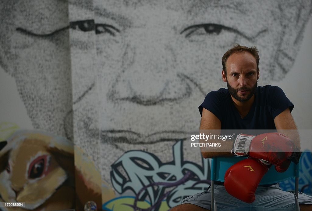 This photo taken on August 1, 2013 shows Shanghai based 34 year-old Belgian artist Phil Akashi posing in front of his portrait of South African peace icon and former boxer Nelson Mandela, which he forged by pounding the wall 27,000 times with a boxing glove which bore the Chinese character for 'freedom', in Shanghai. Mandela, who's 95th birthday earlier this month was marked in South Africa by an outpouring of charitable deeds, with many people offering 67 minutes of service for the 67 years he was in public service, continues to show signs of improvement after two months of hospital treatment. AFP PHOTO / Peter PARKS CAPTION