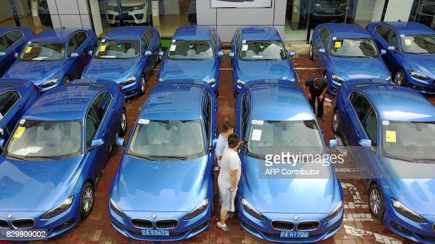 This photo taken on August 10 2017 shows people looking at a BMW 1Series 'sharing car' in Shenyang in China's northeastern Liaoning province Backed...