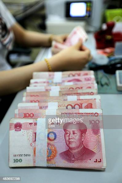 This photo taken on August 11 2015 shows a teller counting Renminbi banknotes in a bank in Lianyungang eastern China's Jiangsu province China has cut...