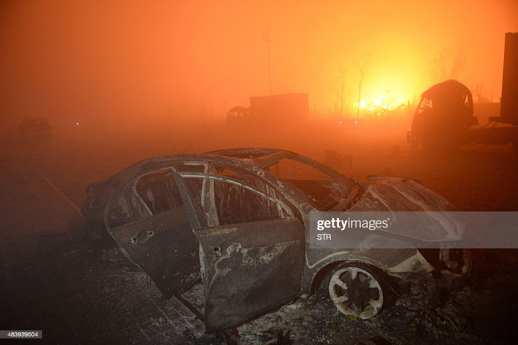 This photo taken on August 13, 2015 shows a destroyed car as a fire continues to burn after a series of explosions at a chemical warehouse hit the city of Tianjin, in northern China. A Chinese military team of nuclear and chemical experts began work on August 14 at the site of two massive explosions in the city of Tianjin, state media said, as pressure grows for authorities to explain the cause of blasts that left 50 dead. CHINA