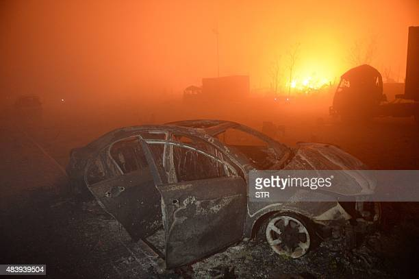 This photo taken on August 13 2015 shows a destroyed car as a fire continues to burn after a series of explosions at a chemical warehouse hit the...