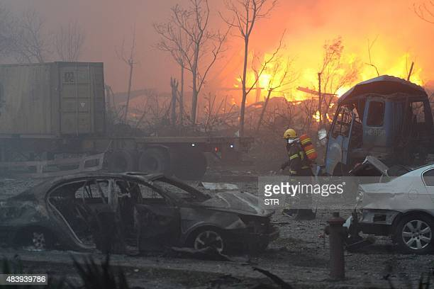 This photo taken on August 13 2015 shows a firefighter walking past damaged vehicles after a series of explosions at a chemical warehouse hit the...