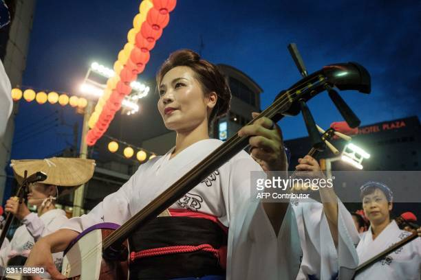 This photo taken on August 13 2017 shows performers playing the shamisen a threestringed instrument during the Awa Odori festival in Tokushima The...