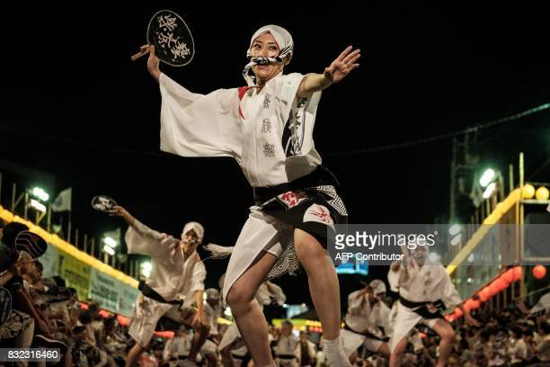 This photo taken on August 14 2017 shows a female dancer of Gejarakuren disguised in a man's costume dancing during the Awa Odori festival in...