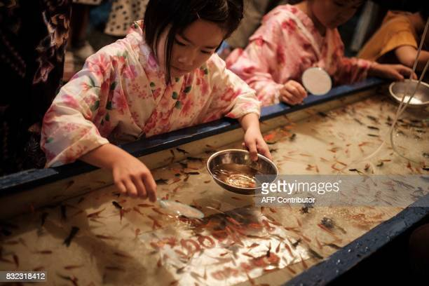 This photo taken on August 14 2017 shows a girl playing a goldfish scooping game at a stand during the Awa Odori festival in Tokushima The fourday...