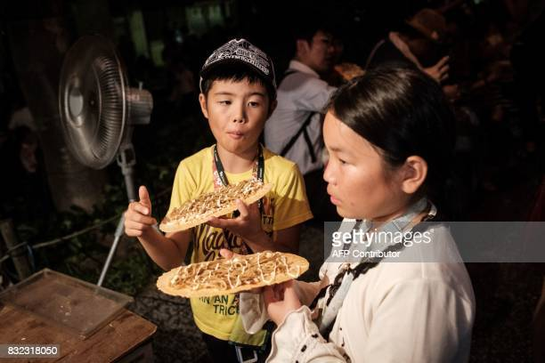 This photo taken on August 14 2017 shows children eating yakisoba noodles during the Awa Odori festival in Tokushima The fourday dance festival...