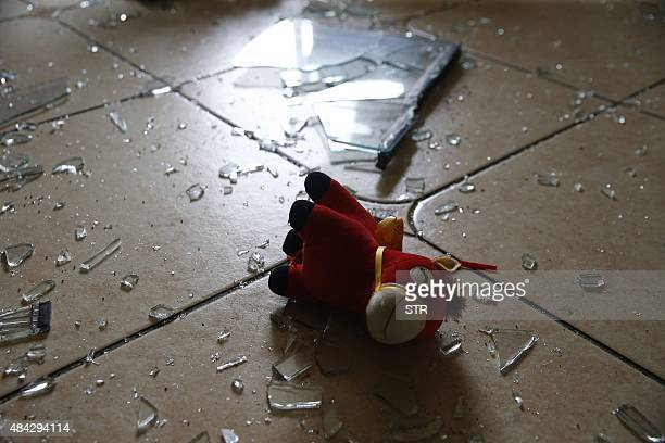 This photo taken on August 15 2015 shows a doll amid shattered glass in a residential building near the site of the explosions in Tianjin Chinese...