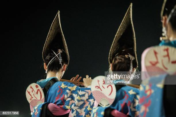 This photo taken on August 15 2017 shows dancers of Ukiyoren playing Japanese flutes during the Awa Odori festival in Tokushima The fourday dance...