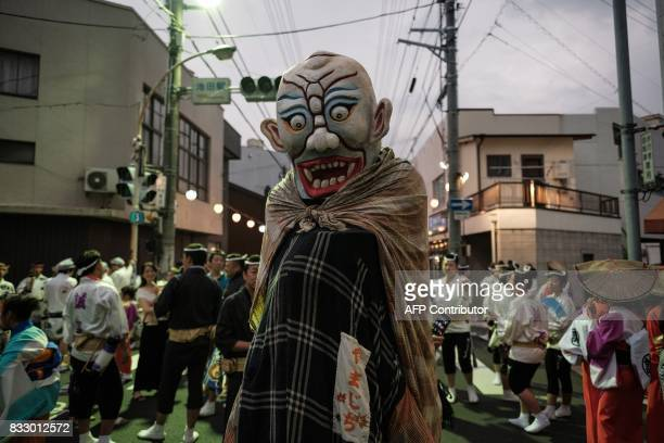 TOPSHOT This photo taken on August 16 2017 shows a dancer disguised as an imaginary monster in Japanese folklore walking on a street at the Ikeda Awa...