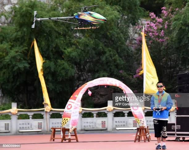 This photo taken on August 20 2017 shows a 12year old boy performing a stunt with a model helicopter during the Laojun Mountain Drone Convention in...