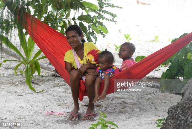 This photo taken on August 20 2017 shows a Byak Betew tribeswoman with her children resting on the beach on the island of Saukabu one of the 1500...