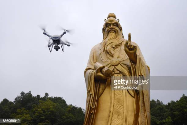 This photo taken on August 20 2017 shows a drone flying in front of the statue of Lord Laozi during the Laojun Mountain Drone Convention in Luoyang...