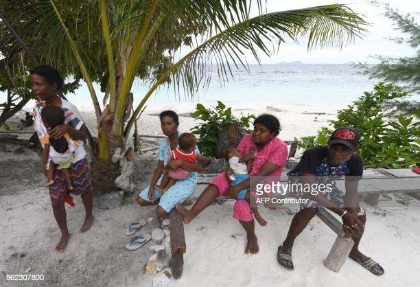 This photo taken on August 20 2017 shows a group of Byak Betew tribeswomen with their babies gathered by the beach on the island of Saukabu one of...