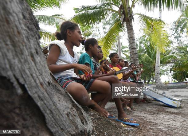 This photo taken on August 20 2017 shows a group of children of the Byak Betew tribe performing songs during a gathering on the island of Saukabu one...