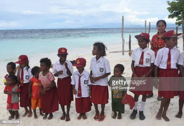 This photo taken on August 20 2017 shows Byak Betew tribal children in their school uniforms as they line up to welcome visitors to the island of...
