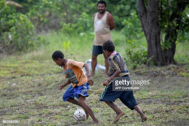 This photo taken on August 23 2017 shows Papuan youngsters playing football on a field in Sorong in Indonesia's Papua Boaz Solossa Indonesia's...
