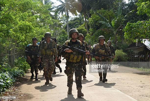 This photo taken on August 26 2016 shows Philippine soldiers walking along a highway as they return to camp at the village of Bongkaong Patikul town...