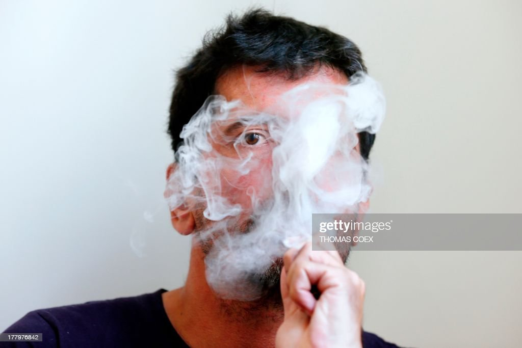 This photo taken on August 26, 2013, shows a person smoking an electronic cigarette in Paris. French consumer rights organization '60 millions de consommateurs' ('60 million consumers') declared on August 26, 2013, that electronic cigarettes 'were not as inoffensive' as most manufacturers claim and 'emit certain components that are potentially carcinogenic'. The organisation criticized manufacturers for false labelling and stated that it had conducted tests which showed the presence of potentially harmful toxic and carcinogenic molecules in electronic cigarette vapor, including formol, acroleine, acetaldehyde, nickel, chrome, and antimoine. The organization called on the government to impose tighter regulations and labelling requirements on manufacturers. AFP PHOTO / THOMAS COEX