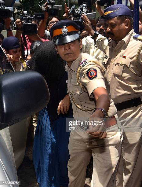 This photo taken on August 29 2015 shows former Indian media executive Indrani Mukherjea being escorted into a police station through a scrum of...