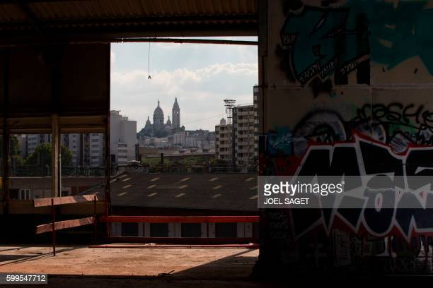 This photo taken on August 30 2016 shows the construction site of a future migrant camp in northern Paris with the Basilica of the Sacred Heart in...