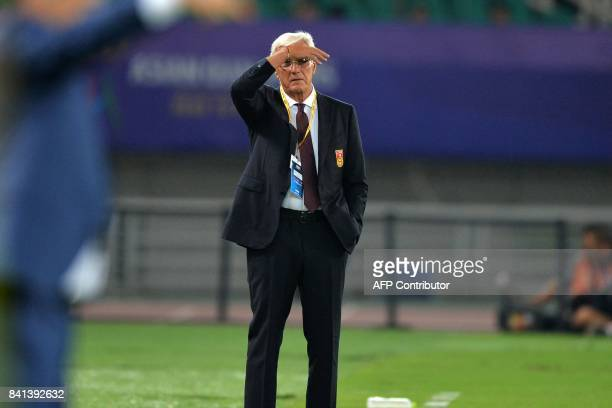 This photo taken on August 31 2017 shows China's coach Marcello Lippi watching from the sidelines during the World Cup football qualifying match...