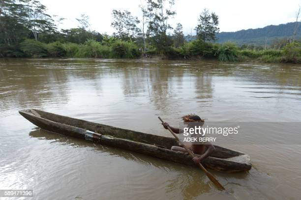 This photo taken on August 7 2016 shows Markus Mabel paddling a canoe near Wogi village near Wamena the longisolated home of the Dani tribe high in...