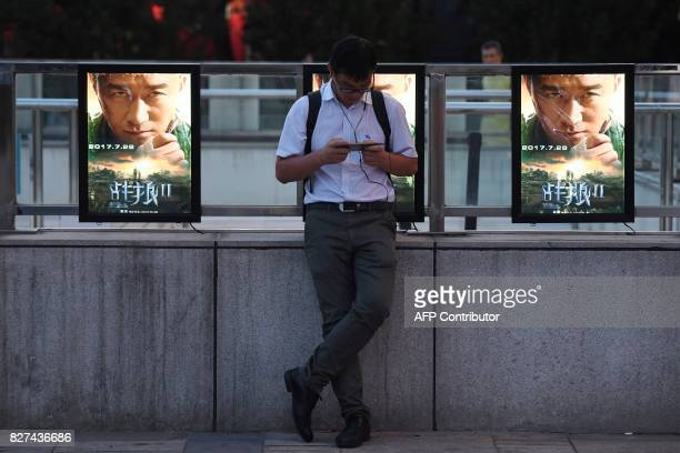 This photo taken on August 7 2017 shows a man standing in front of movie posters for 'Wolf Warriors 2' in Beijing A Chinese action film that depicts...