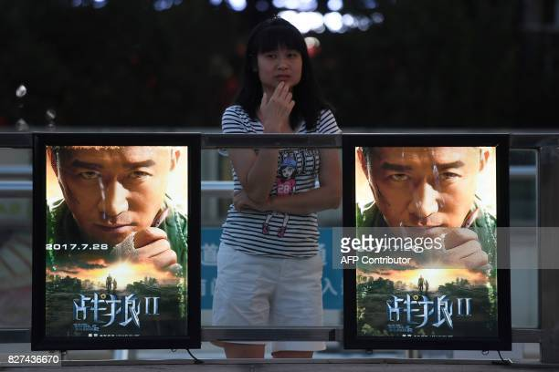 This photo taken on August 7 2017 shows a woman standing next to movie posters for 'Wolf Warriors 2' in Beijing A Chinese action film that depicts...