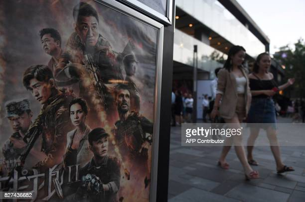 This photo taken on August 7 2017 shows people walking past a movie poster for 'Wolf Warriors 2' in Beijing A Chinese action film that depicts the...