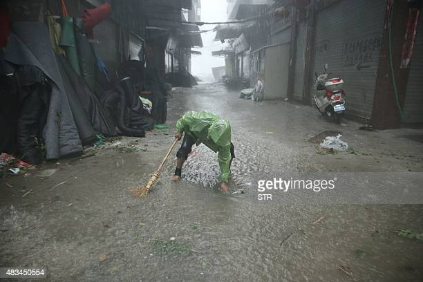 This photo taken on August 8 2015 shows a man dredging a sewer as Typhoon Soudelor brought heavy rain to Ningde eastern China's Fujian province A...