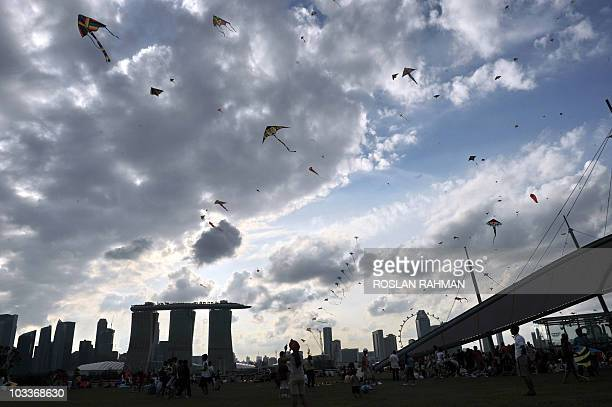This photo taken on August 9 2010 shows people flying their kites at the Marina Barrage roof top during the 45th National Day anniversary...