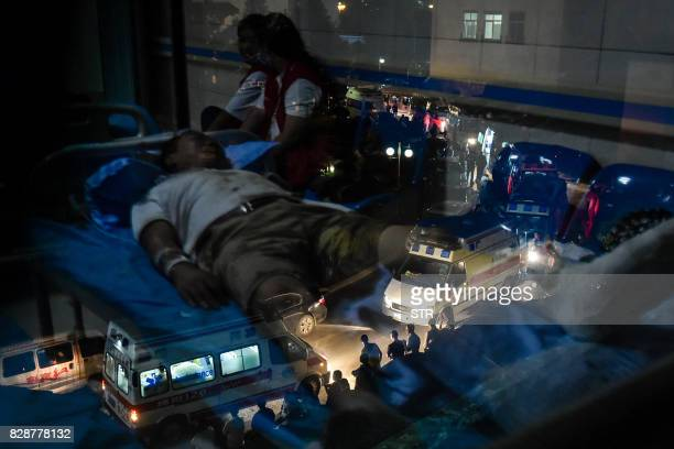 TOPSHOT This photo taken on August 9 2017 shows an earthquake survivor lying on a hospital bed reflected in a window as ambulances are seen outside...