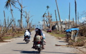 This photo taken on December 11 2012 shows a family on a motorcycle riding past destroyed coconut trees in Cateel in Davao Oriental province after...