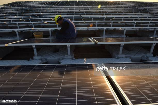 This photo taken on December 11 2017 shows a Chinese employee working on a floating solar power plant in Huainan a former coalmining region in...
