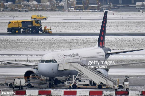 This photo taken on December 11 2017 shows a snow truck clearing snow from the tarmac of Brussels Airport after several flights are delayed and...