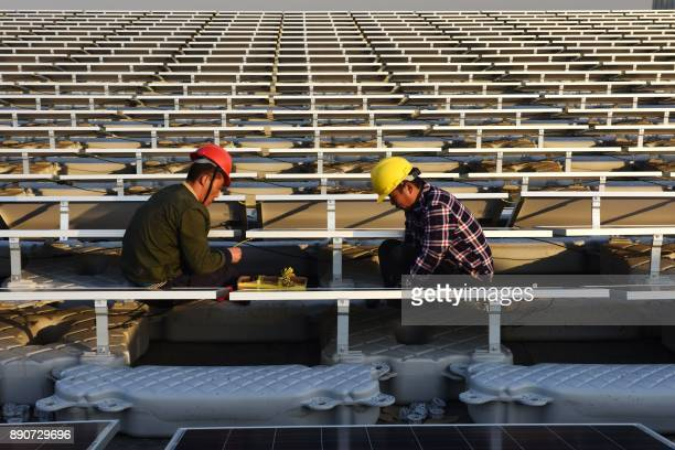 This photo taken on December 11 2017 shows Chinese employees working on a floating solar power plant in Huainan a former coalmining region in China's...