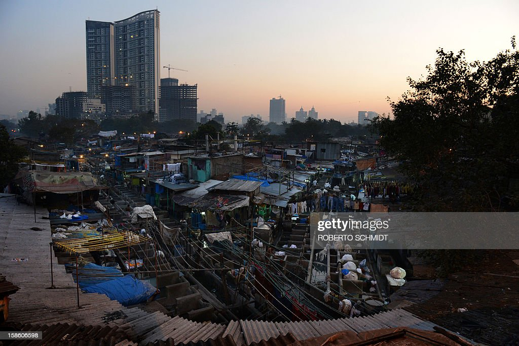 This photo taken on December 13, 2012 shows an open air laundry facility known as the Dhobi Ghat next to residential highrises in the early morning in Mumbai. This 25-acre (10-hectare) space is a chaotic conglomeration of rows of open-air concrete wash pens, each with its own flogging stone and rooms where the washermen, also known as 'dhobiwallahs', sleep and work. Many of the over 700 families that make a living out of this Dhobi Ghat, who had followed their father into the business, a life of dunking, thrashing and drying close to 1,000 items of clothing each day for just 7 USD, are worried about the future as the workload has gone down considerably. Most ordinary Indians who have seen their disposable incomes rise as the country's economy expands, have dispensed with the services of the dhobiwallahs for good since most modern homes are equipped with a washing machine. AFP PHOTO / Roberto Schmidt